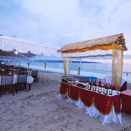 Dine on the beach at Jimbaran Bay as the sun sets over the ocean.