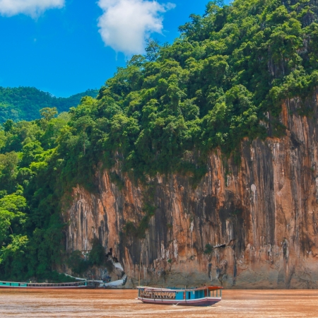Embark on a riverboat trip along the mighty Mekong River to visit the famous and sacred Pak Ou Buddha Caves, filled with thousands of Buddha images.