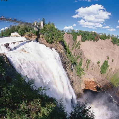 """This natural phenomenon is definitely not to be missed! At 83 m high (30 m higher than Niagara Falls) Montmorency Falls can be seen from all the way across the St. Lawrence River in Lévis! But the best views are from Parc de la Chute-Montmorency, where you can feel the full force—and spray—of the falls for yourself. In winter the spray freezes at the foot of the falls to form a huge """"sugar loaf,"""" another intriguing Québec City attraction."""